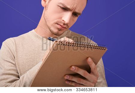 Concentrated Author Writes An Action Plan Or Solves A Problem In A Paper Notebook . Redactor Stands