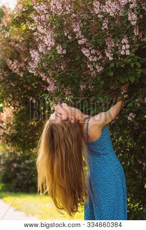 Portrait Of Girl With Blond Hair And Threw Back Head And Blue Dress Near Lilac, Summertime