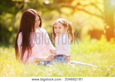 Happy mother and daughter in the summer park. Beauty nature scene with family outdoor lifestyle. Happy family resting together on green grass, having fun outdoor. Happiness and harmony in family life