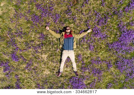 Bearded Man Lies On The Field In Violets Top-down View