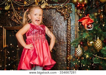 Little girl tells a poem standing by a beautiful  Christmas tree. Merry Christmas and Happy New Year!