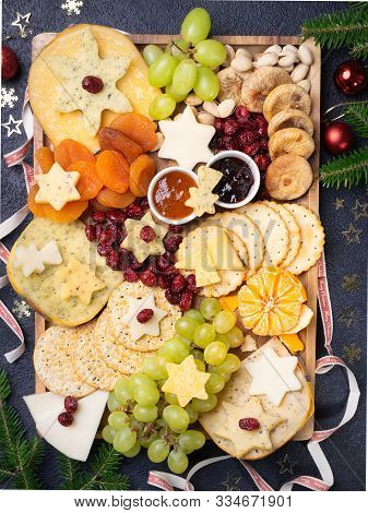 Christmas Cheese board appetizers platter with various types of cheese, crackers, jam, fruits and pistachios on a dark background. Overhead view, cope space.