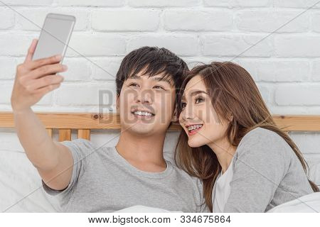 Happy Asian Lover Sitting And Using The Digital Smart Mobile Phone To Selfie On The Bed Of Bedroom A