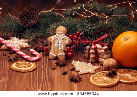 Christmas gingerbreads. Christmas decorations. Handmade cookies, fir branches with decorations on the wooden table.  Christmas and New Year treats.