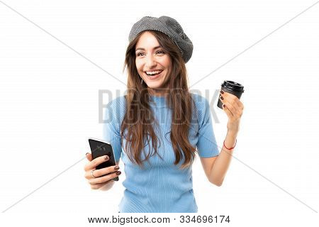 Caucasian Female With Cap Drinks Coffee And Smiles, Picture Isolated On White Background.