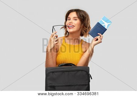 travel, tourism and vacation concept - happy laughing young woman in mustard yellow top with air ticket, carry-on bag and passport over grey background