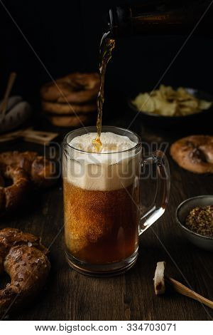 Beer Pouring In Glass With Pretzels, Bratwurst And Snacks On Rustic Wooden Table