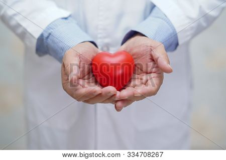 Doctor Holding Red Heart In His Hand In Nursing Hospital Ward : Healthy Strong Medical Concept
