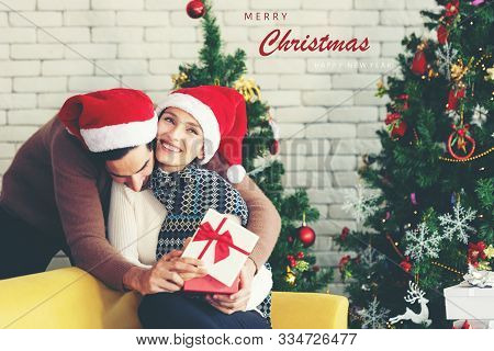 Merry Christmas. Boyfriend Surprising His Girlfriend With Christmas Gift. Young People Couple Celebr