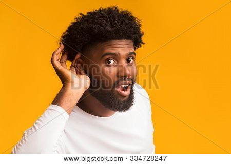 Curious Interested African American Man Holding Hand Near Ear And Trying To Hear Information, Orange