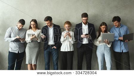 Businesspeople With Gadgets Standing In Row Over Grey Wall, Panorama