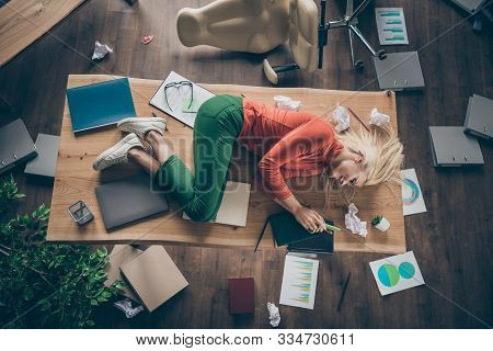 High Angle Above View Photo Of Corporate Messy Atmosphere Unorganized Blond Business Lady Lying Tabl
