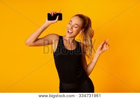 Music App. Sporty Woman In Wireless Earbuds Holding Smartphone And Dancing Over Yellow Background. S