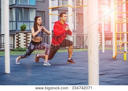 Fitness, Sport, Exercise, Lifestyle Concept. Mixed Race Young Man And Woman Doing Exercise On Street