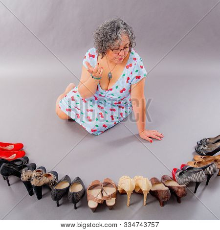 Undecided Mature Woman Choosing From A Variety Of Shoes, Group Of Heeled Shoes In Different Fashion
