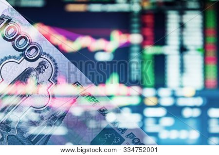 The Russian Ruble On The Background Of The Trading Chart. A Thousand Rubles Close-up. Fall Or Rise O