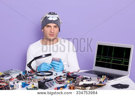Young Computer Specialist Repairing Broken Smart Phone, Being Ready To Dismantle It, Siiting At Tabl