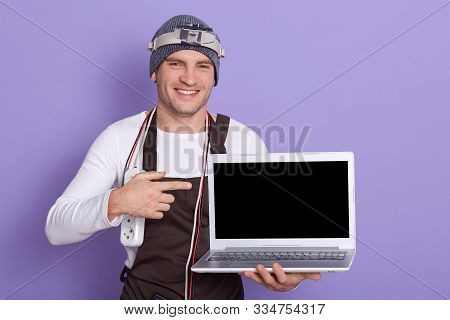 Image Of Cheerful Positive Radioman Holding Laptop With Blank Screen, Making Gesture, Showing With F