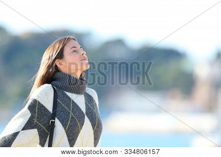 Relaxed Woman Wearing Jersey Breathing Deeply Fresh Air On The Beach In Winter