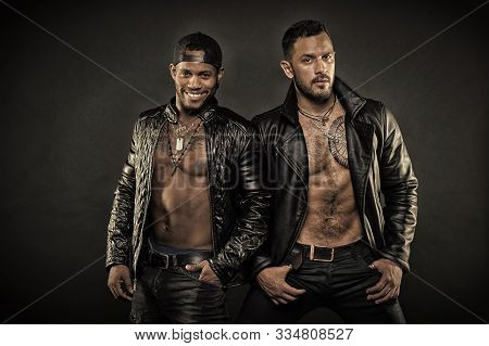 Bearded Man Holding Hands In Pockets. African Man Wearing Cap Backwards. Two Male Models In Leather
