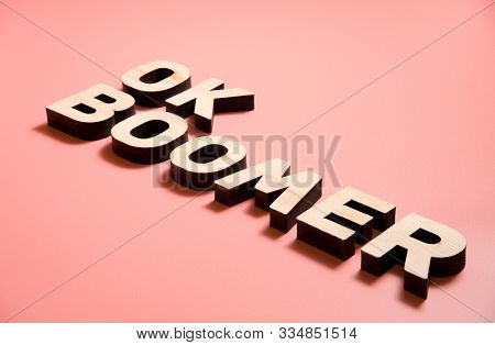 OK Boomer. Internet meme popular among young people. Wooden letters on pink background.