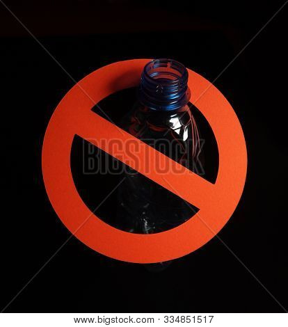 Empty blue plastic bottle in a stop sign on black background. Concept of stop plastic pollution, global warming, recycling plastic, plastic free.