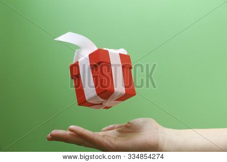 Red Gift Box With A White Bow On A Green Background.
