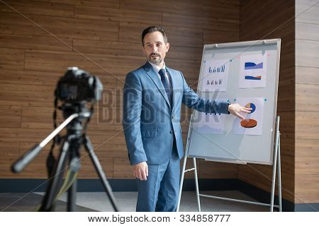 Mature Affluent Businessman Standing Near Smart Board And Filming Blog