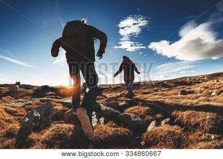 Couple Of Hikers Run And Jump Against Sunset Mountains And Sky