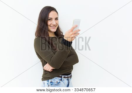 Happy Friendly Beautiful Woman Holding Cellphone And Looking At Camera. Young Woman In Casual With M