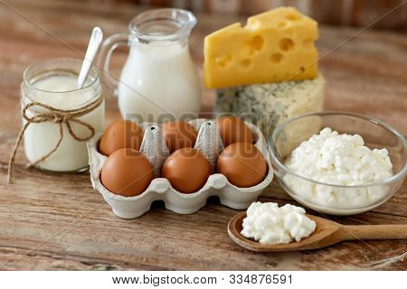 food and eating concept - close up of cottage cheese, jug of milk, homemade yogurt and chicken eggs on wooden table