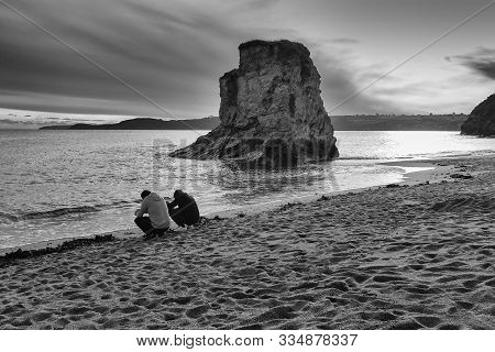 Two Men Surfing With Their Mobile Phones On A Beach During A Beautiful Sunset At St. Austell, Cornwa