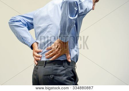 Closeup Elderly Man With Pain In Kidneys Isolated On A Gray Background. Old Man With Back Ache Clasp