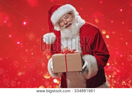 Jolly Santa Claus holds a gift box  over festive red background. The atmosphere of celebration and magic, lights and sparkling around. Merry Christmas and Happy New Year! Copy space.