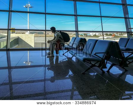Passenger Sits In The Departure Zone Of The Airport And Looks At The Runway Through The Panoramic Wi