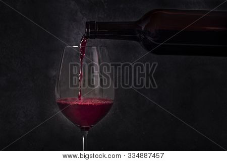Wine Poured Into A Glass From A Bottle, On A Dark Background With Copy Space