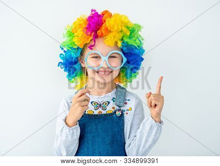 Smiling little girl in multicolor wig and paper glasses raising pointing finger
