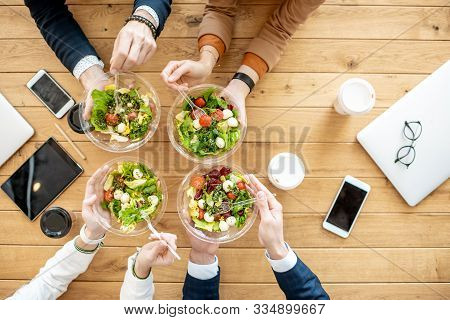 Office Workers During A Business Lunch With Healthy Salads And Coffee Cups, View From Above On The W