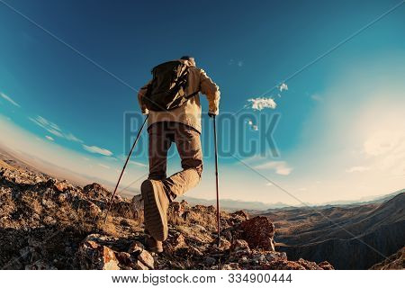 Hiker Man Goes In Mountains Area At Sunset Time