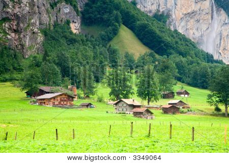 Houses and barns are close to a steep rocky mountain near Lauterbrunnen Bern Canton Switzerland. poster