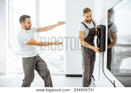 Two professional workmen in workwear installing luxury audio system in the white living room. Home appliances installation concept poster