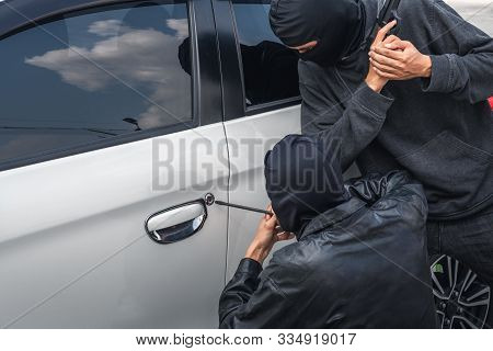 Two Robber Thief Criminal Bandits In Robes Standing Next Gun Robbed And Forced Open The Car Door. To