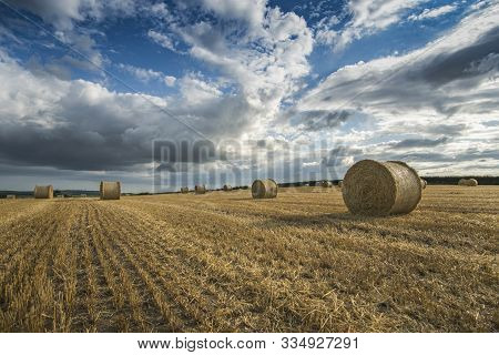 Harvest Time Bales Of Straw In Fields, With Dramatic Cloudy Sky, Cornwall, Uk