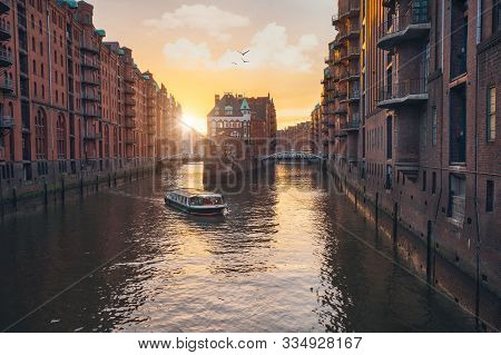 Famous Hamburg Warehouse District. Water Castle Palace And Tourist Boast In River In Sunset Golden L