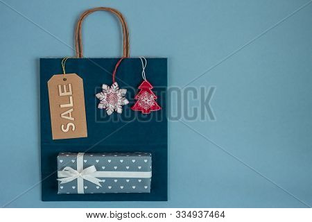 Blue Paper Craft Bag With Sale Tag And Holiday Christmass Decoration