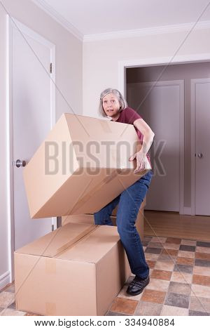 Woman Lifting A Big Box In A House