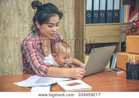Pretty Young Single Mom Working At Home On A Laptop Computer While Holding Her Baby Girl Sitting On