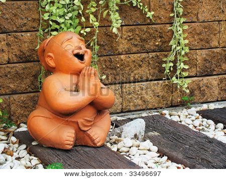 A baked clay boy statue smailing and sawasdee