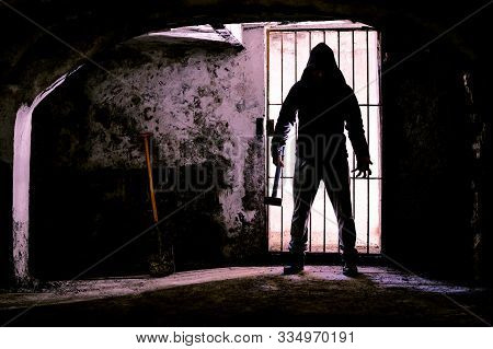 Scary Dark Man Holding Hammer Inside Dungeon - Silhouette Of Serial Killer Standing In Creepy Prison