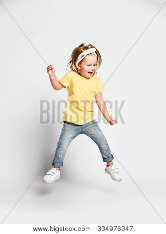 Active Gamboling Happy Screaming Kid Baby Girl Blonde In Yellow T-shirt, Blue Jeans And Sneakers Is